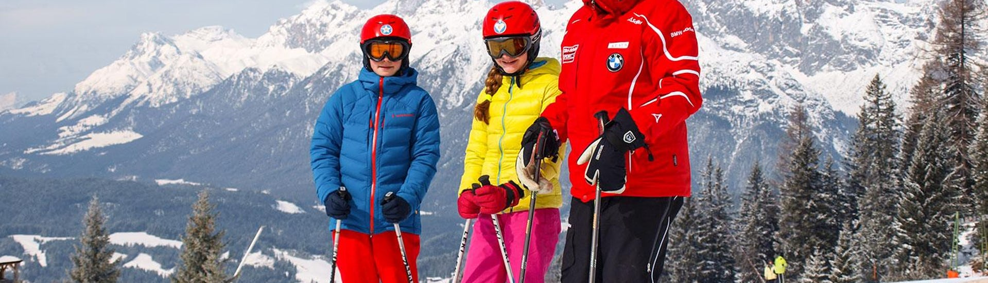 Ski instructor with two teenagers at the slope with mountains at the background