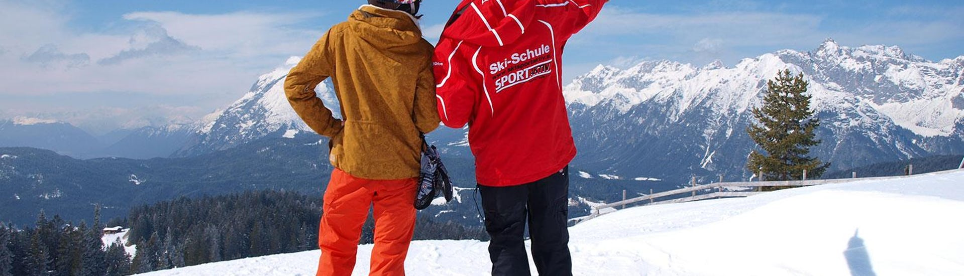 Snowboardinstructor and the student with back to the camera and ski instructor pointing at the mountain panorama