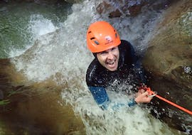 """A man participating to Canyoning """"Sensation"""" - Canyon d'Angon with Térreo Canyoning is going down the waterfall."""