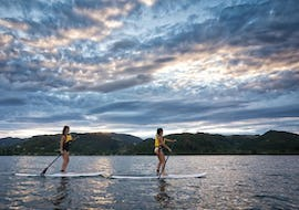 Two participants of the Paddle Board Rotorua - Adventure Tour organized by Paddle Board Rotorua are enjoying the sunset floating on Lake Okareka before entering the glow worm caves.