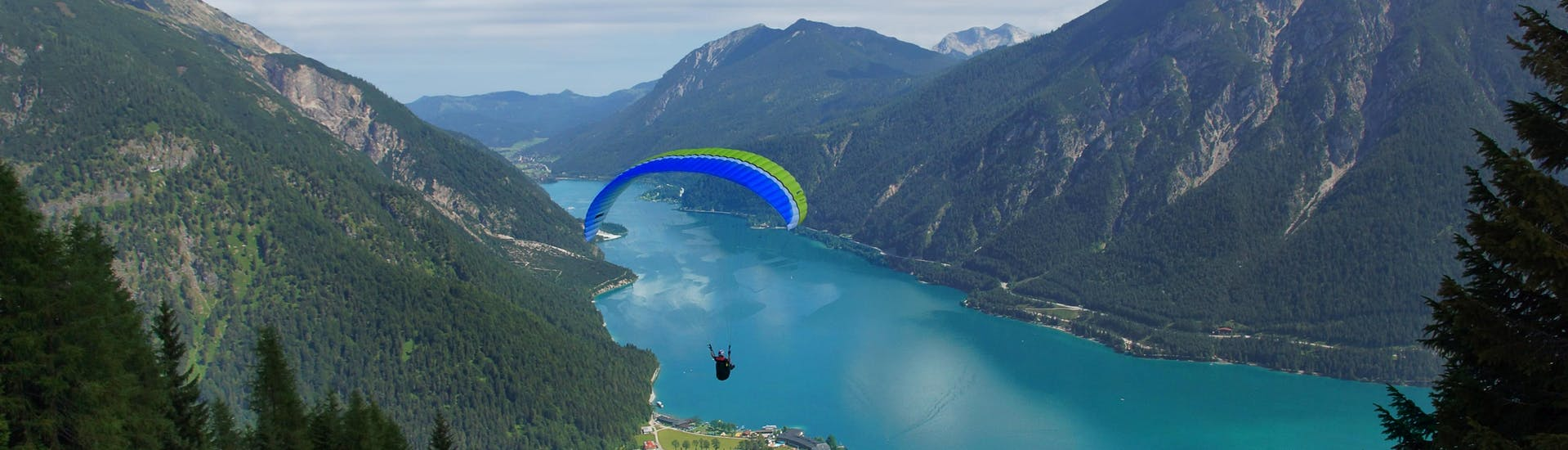 A tandem master and his passenger are sailing through cloudy skies while paragliding in Achensee.