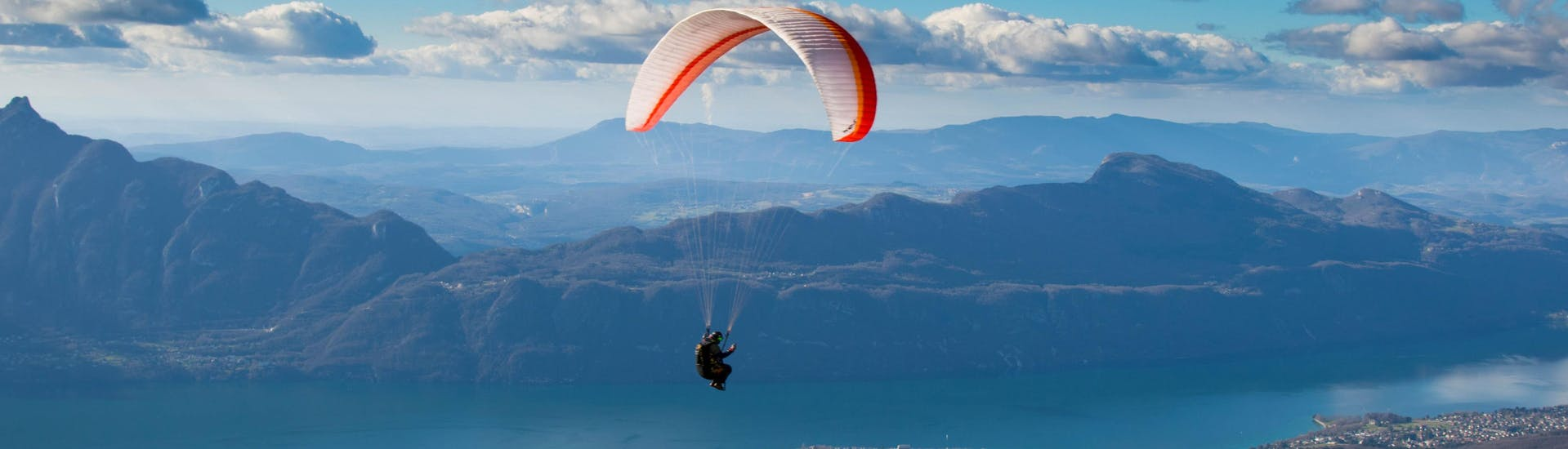 An image of a paraglider gently floating over the Bourget lake while paragliding in Aix-Les-Bains.
