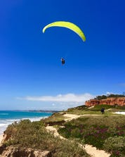 A view of a flight flying above the ocean and the beach where you can do paragliding in Albufeira.