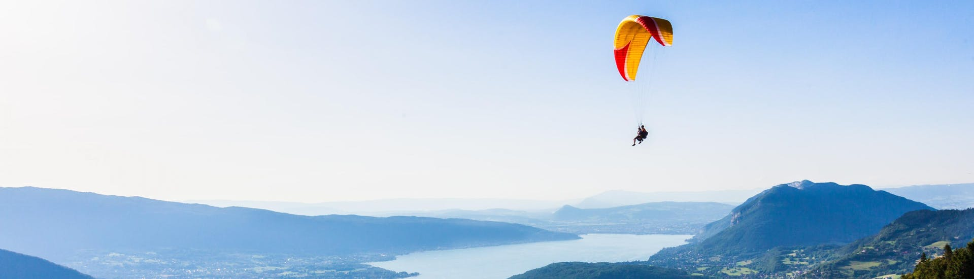 A tandem master and their passenger are gently gliding through the skies while paragliding at Lac d'Annecy.