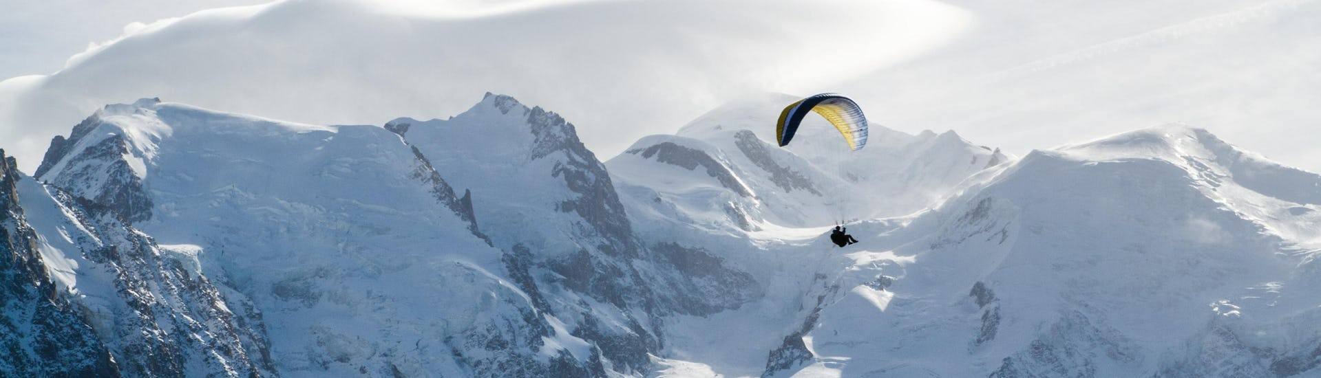 A person is doing a paragliding flight in the Chamonix valley with the snowy mountains in the background.