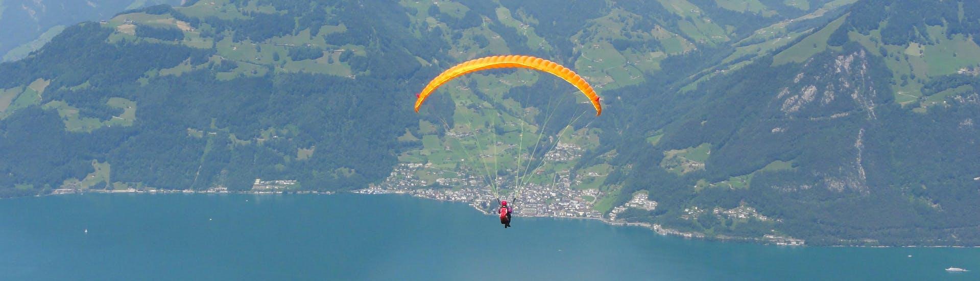 Un parapentiste est émerveillé par le paysage lors d'un vol en parapente biplace dans la célèbre destination de parapente Emmetten-Lucerne.