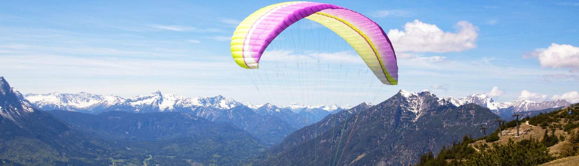A tandem master and his passenger are sailing through cloudy skies while paragliding in Garmisch-Partenkirchen.
