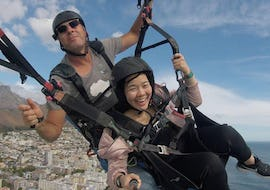 A girl is taking selfies her flight with her pilot from Icarus Tandem Paragliding during the Paragliding in Cape Town from Lion's Head.