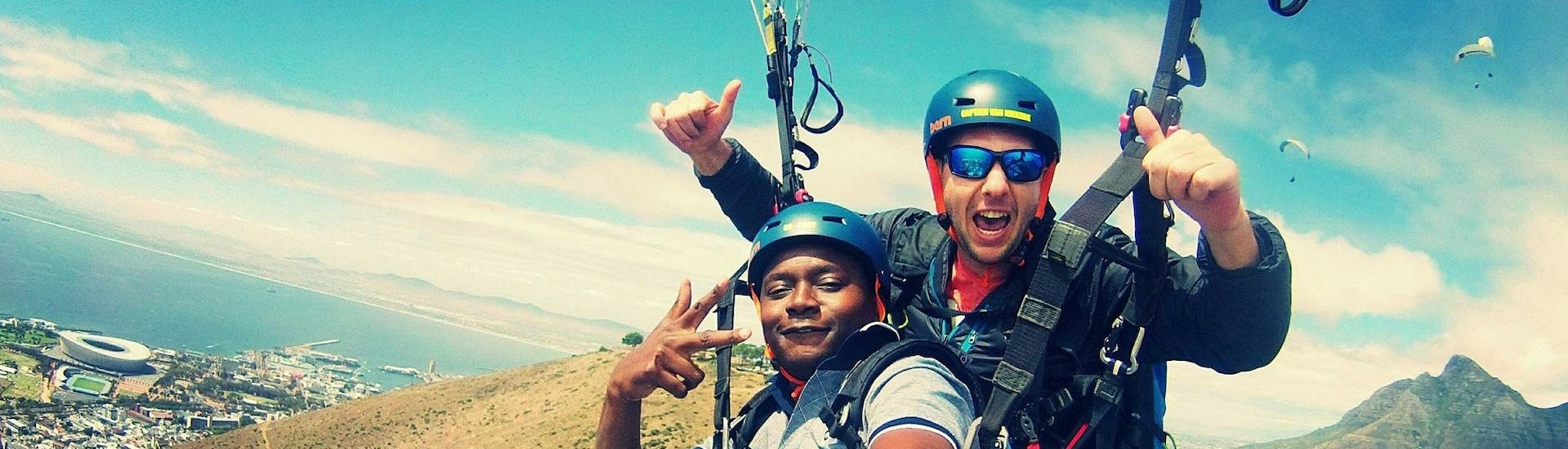 During the Paragliding in Cape Town from Lion's Head, a tourist is enjoying his first paragliding flight with his professional pilot from Icarus Tandem Paragliding.