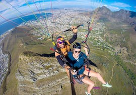 A young woman is flying over Lion Head's with her experienced tandem pilot from Parapax Paragliding Cape Town while Paragliding in Cape Town from Signal Hill.