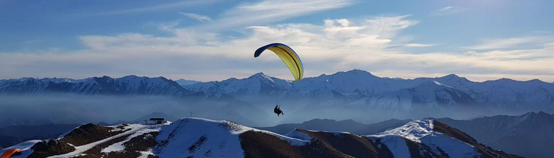 A paraglider from Skytrek Queenstown is flying over snow-capped mountains while Paragliding in Queenstown - Winter.