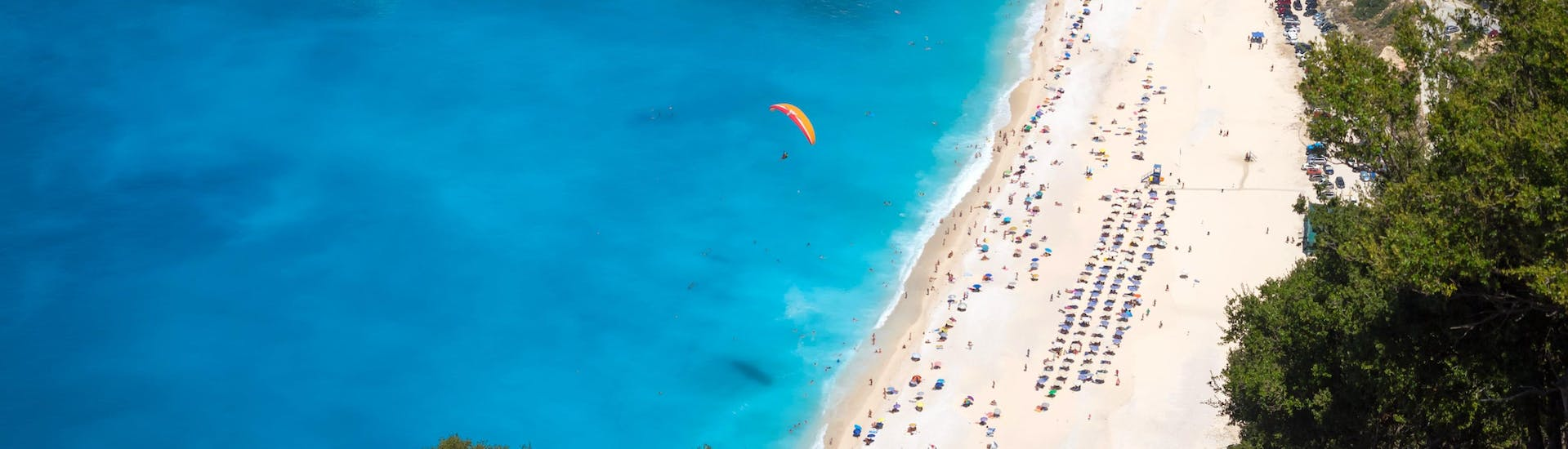 A tandem master and his passenger are sailing through cloudy skies while paragliding in Kefalonia.