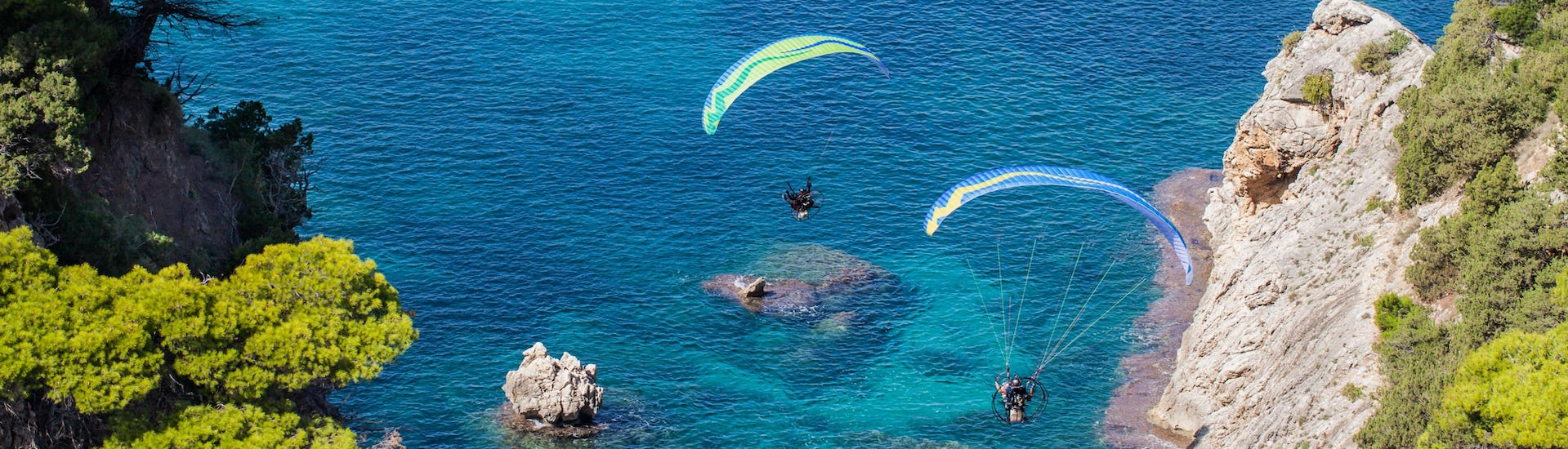 A tandem master and his passenger are sailing through cloudy skies while paragliding in Crete.