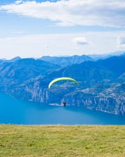 A lone paraglider can be seen floating gently over the picturesque landscape while paragliding at Lake Garda.