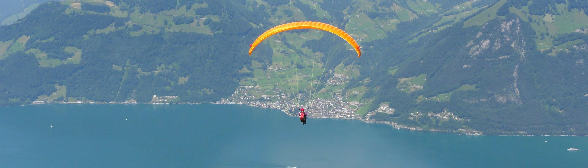 A tandem master and his passenger are sailing through cloudy skies while paragliding in Lucerne.