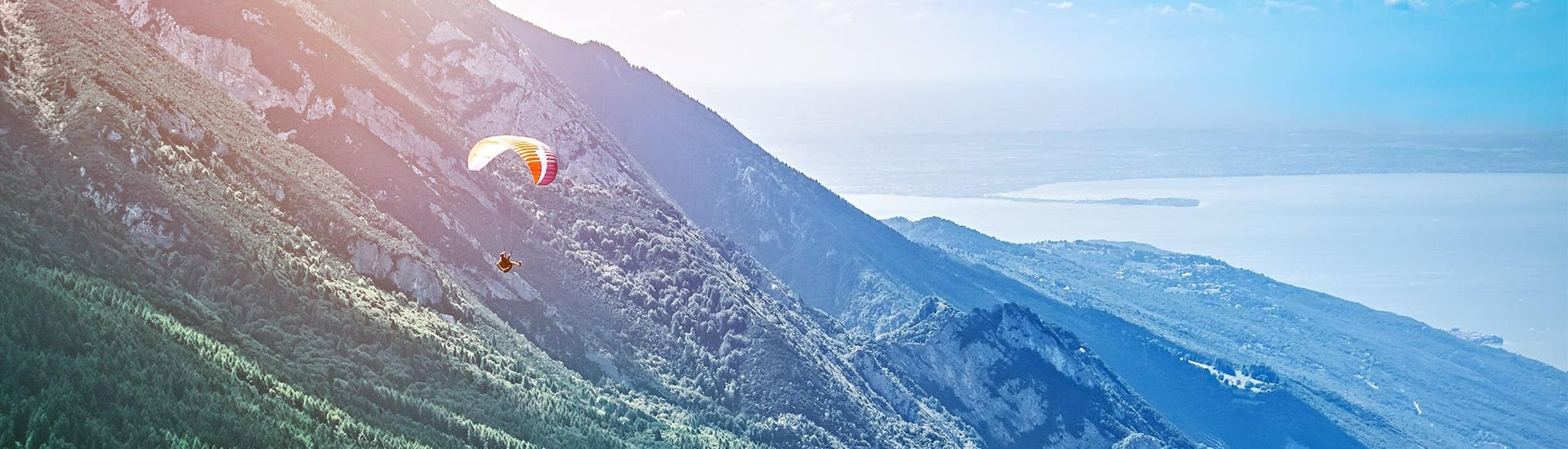 A paraglider can be seen flying towards Lake Garda while paragliding from Monte Baldo.