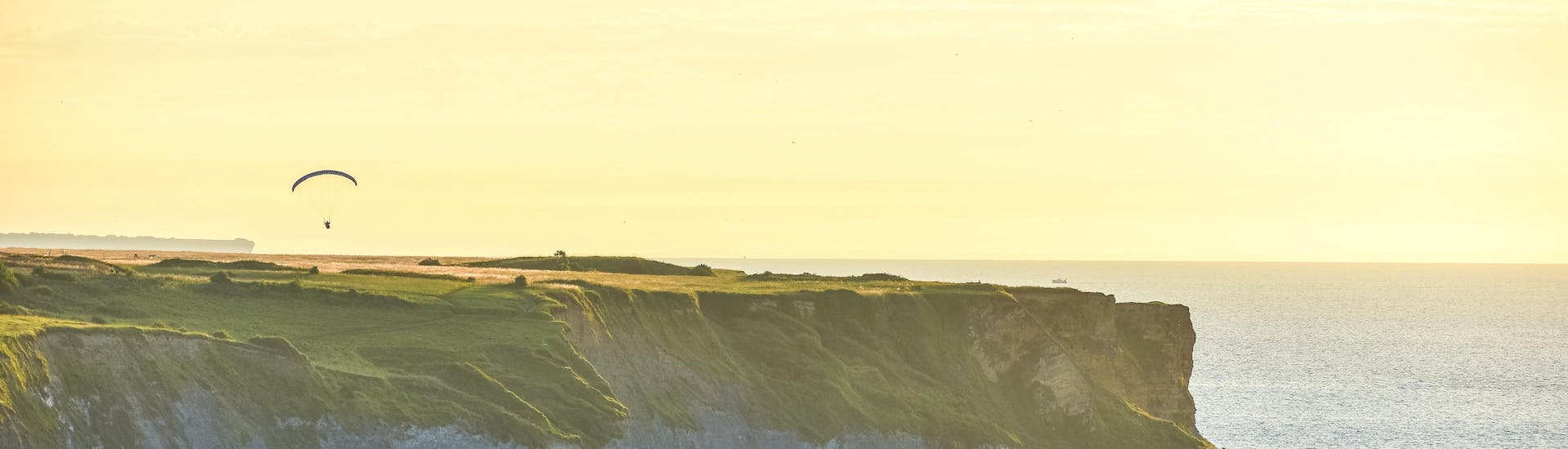 A man is doing a paragliding flight over the cliffs overlooking the sea in Normandy.