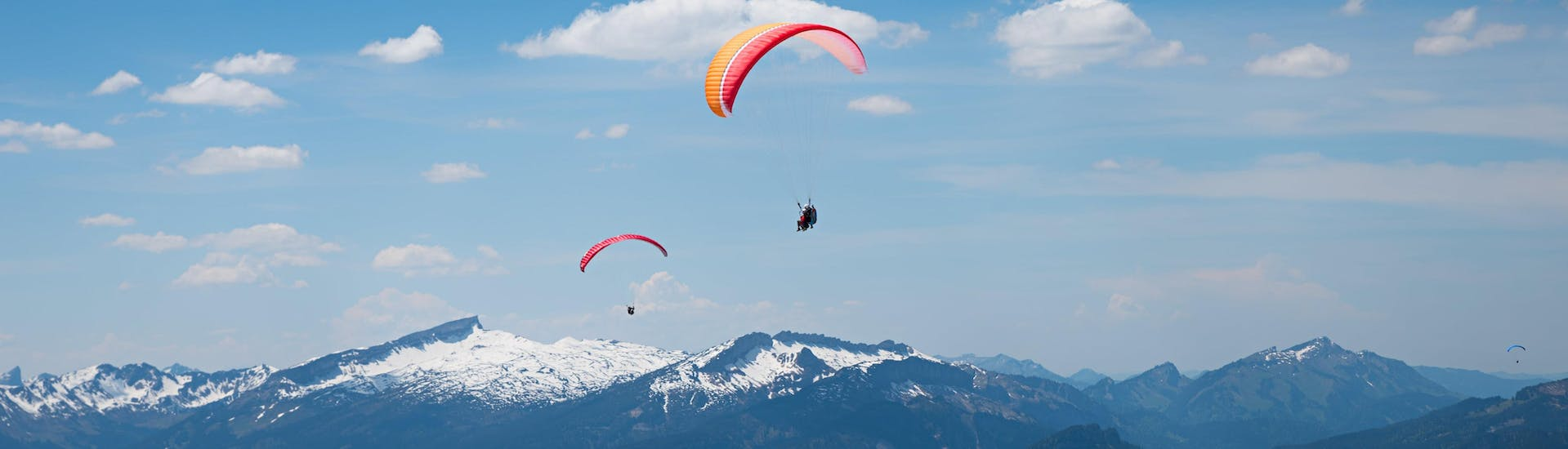 A tandem master and his passenger are sailing through cloudy skies while paragliding in Oberstdorf.