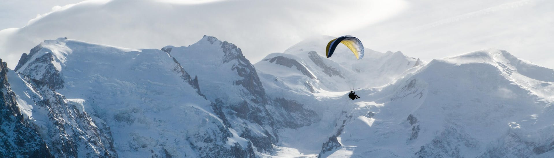 A person is doing a paragliding flight in the Chamonix valley from Plan Praz with the snowy mountains in the background.