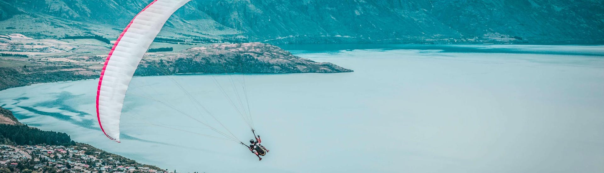 A tandem master and his passenger are flying over Lake Wakatipu while paragliding in Queenstown, New Zealand.