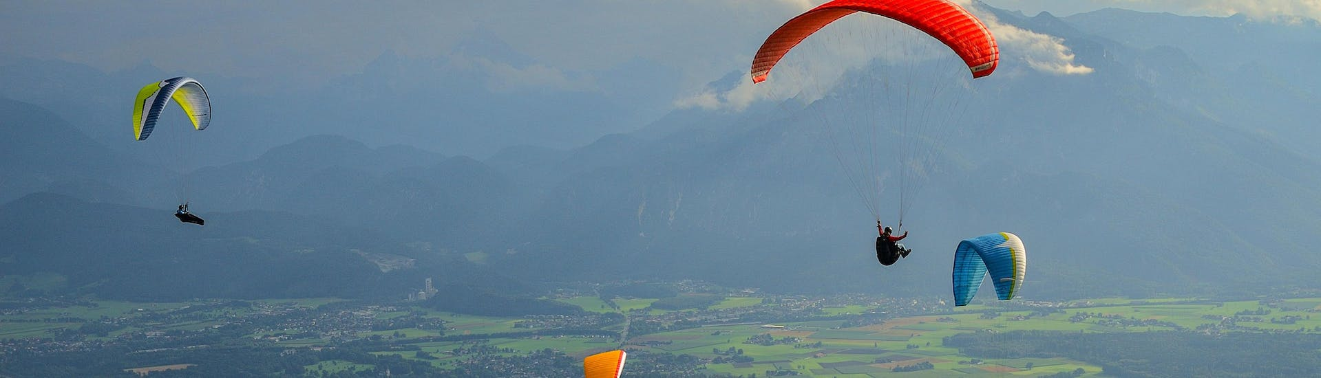 A tandem master and his passenger are sailing through cloudy skies while paragliding in Salzburg.