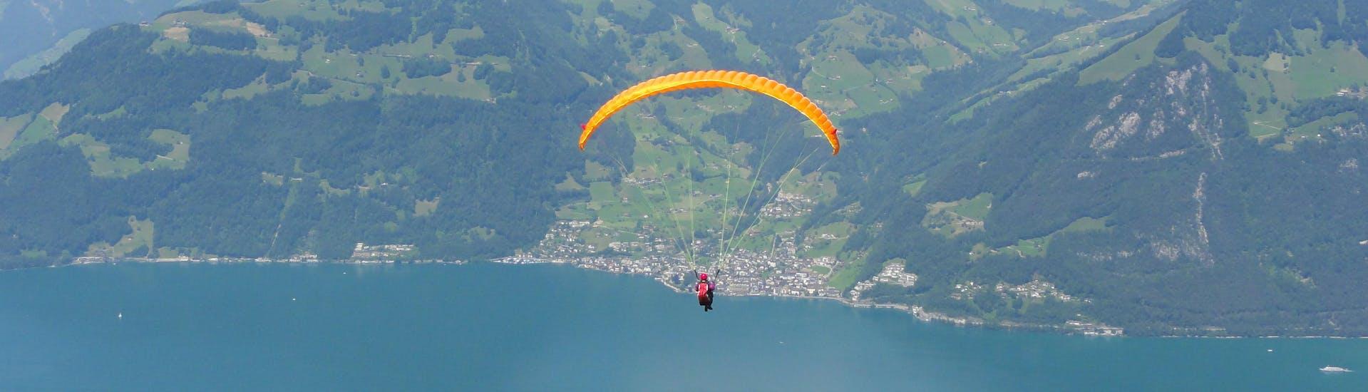 Un parapentiste est émerveillé par le paysage lors d'un vol en parapente biplace dans la célèbre destination de parapente Lac des Quatre-Cantons.