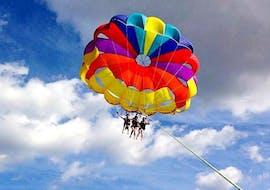 Drei Freunde genießen die wunderbare Aussicht auf die maltesische Küste von oben, während sie beim Parasailing in der Mellieha Bay mit Oh Yeah Malta in die Luft steigen.
