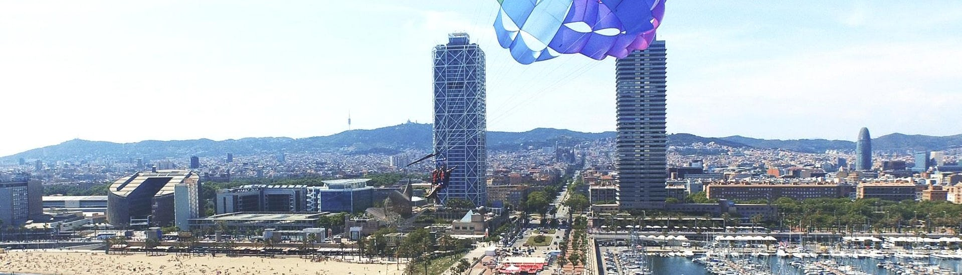 Two friends are marvelling at the panoramic views of Barcelona during the Parasailing - Barcelona organised by Five Star Barcelona.