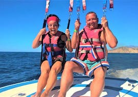 Two participants of the Parasailing organized by Carlos Water Sports Benidorm are smiling at the camera after landing from the sky above Benidorm.