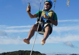 During the Parasailing in Paihia - For 1 Person, a man towed by a motorboat from ay of Islands Parasail is enjoying the 360-degree views of the Bay of Islands.