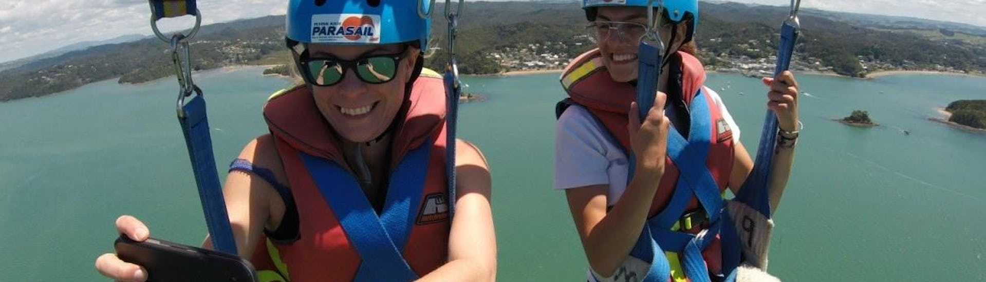 During the Parasailing in Paihia - For 2 People, two friends are enjoying the amazing views while being towed by a motorboat from Bay of Islands Parasail.