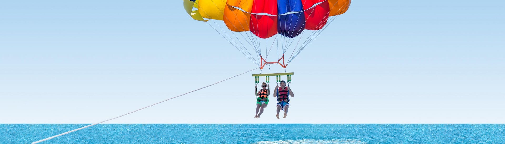Friends are parasailing in the blue sky over the ocean
