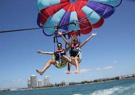A couple is having a great time during the Parasailing in Gold Coast - For up to 3 People offered by Gold Coast Watersports.