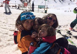 The young skiers hug their ski instructor during the private ski lessons for families - all levels of ski school Escuela Esquí y Snowboard Valle de Benás.