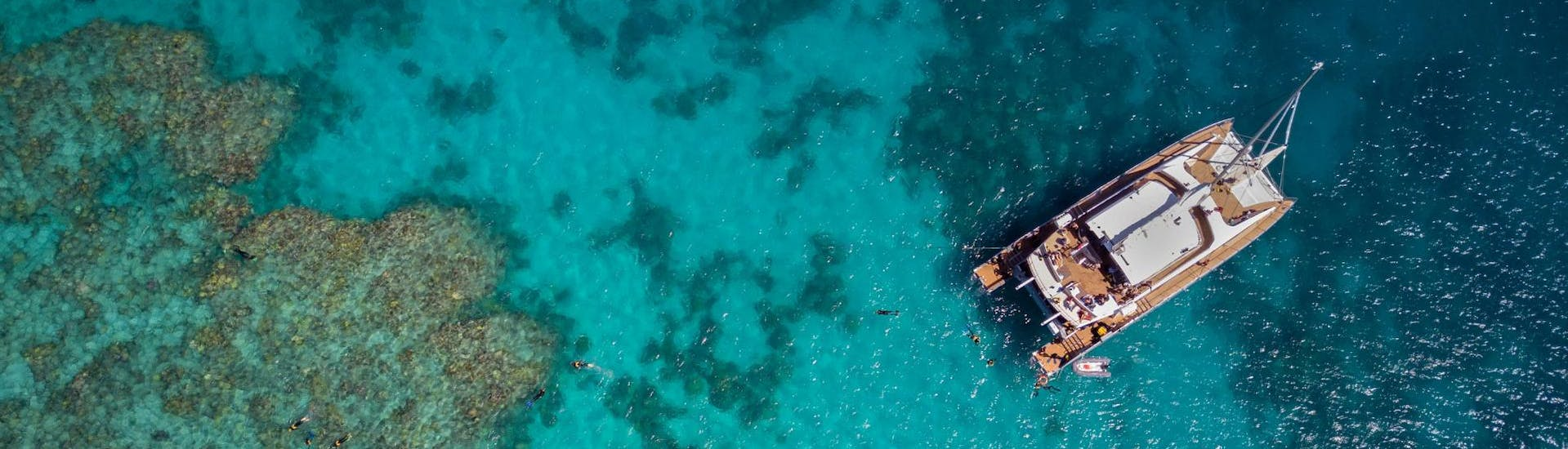 Tourists are snorkelling on the Great Barrier Reef during the stop of the catamaran of Passions of Paradise.