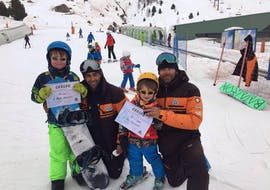The children proudly show the certificate they have earned in their private ski lessons for kids (3-16 years) - all levels of the ski school Escuela Esquí y Snowboard Valle de Benás.