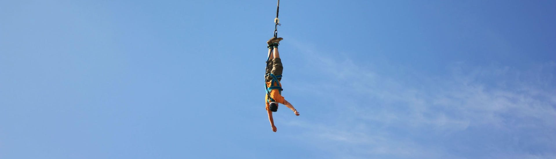 A bungee jumping enthusiast hangs head upside down after doing his Pendulum Jump from the Viaduc Lavilledieu (25m) with Torrents & Granit.