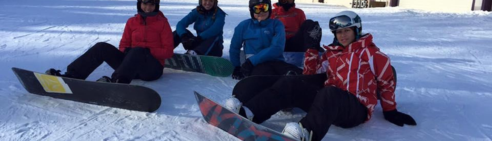 Group of snowboarders sitting in the snow