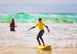 A boy is surfing during the private Surfing Lessons on Salie Beach for All Levels with Pyla surf school.