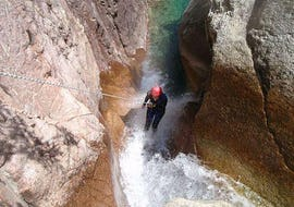 A woman is abseiling down a waterfall during a Canyoning in Canyon de Pulischellu - Discovery tour with Corsica Madness.