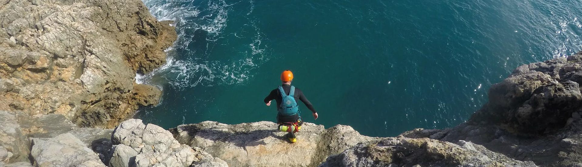 "A participant of the Coasteering ""Adventure"" Tour in Sagres is getting ready to jump off from a high cliff on the side of an experienced guide from Poseidon Adventure"