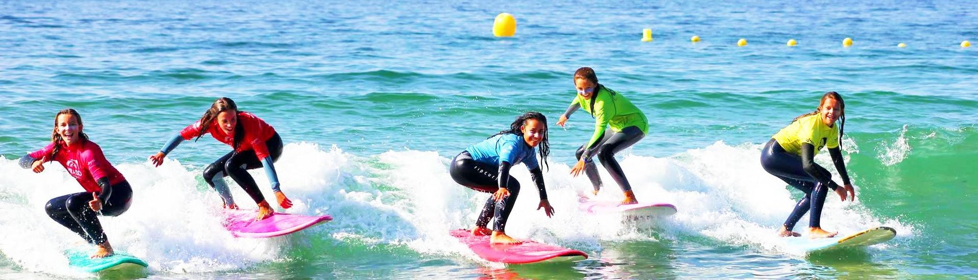 A group of surfers enjoy surfing on the beautiful beach together with Prado Surf Patos.
