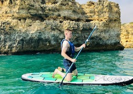 A young man is kneeling on a SUP board during the Praia de Coelha Boat Tour with Kayak or SUP with SeaAlgarve Albufeira.
