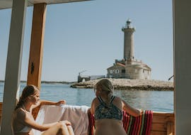 Two girls are enjoying the view of the lighthouse on their Private Boat Trip to Kamenjak with Rio Boat Pula.