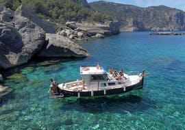 A boat from Take Off Ibiza is floating in the crystal clear waters during a private boat trip along the coast of Ibiza.