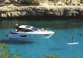 A person paddle surfs whilst on a private boat trip to Formentera with Charteralia Ibiza.