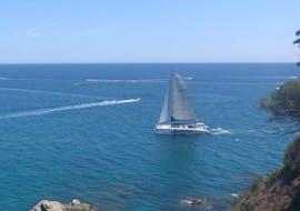 Un bateau est au milieu des eaux bleues lors de la sortie privée en catamaran à la Costa Brava avec Snorkeling.