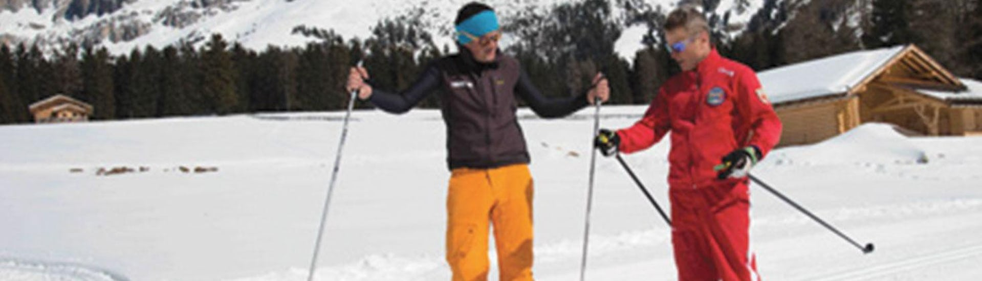 A cross-country skiing instructor from Carezza Skischool is explaining his pupil how to improve the technique during Private Cross Country Skiing Lessons - All Levels.