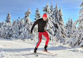 Un participant au Cour particulier de ski de fond - Tous Niveaux avec l'école de ski Schneesportschule Black Forest Magic Feldberg passe à travers le paysage enneigé de la Forêt-Noire.