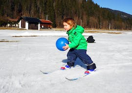 A young boy is learning to ski playfully during Private Cross Country Skiing Lessons for Families with the ski school Schneesportschule Morgenstern.
